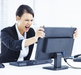 Portrait of a young business woman holding computer monitor in anger